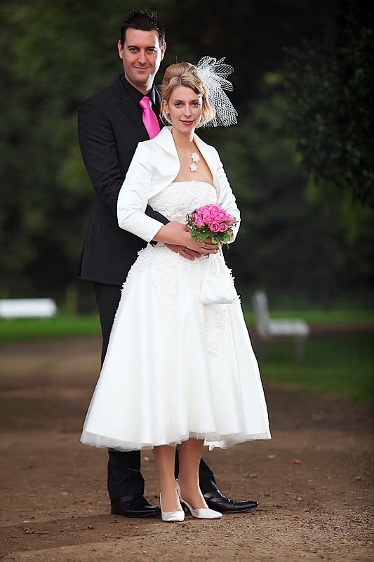 Pinkes Bouquet am schwarzen Anzug und weisses Hochzeitskleid